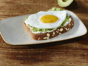 fried egg on avocado spread on toast on a plate