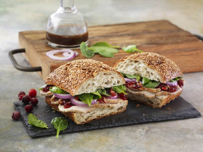 Balsamic Cranberry Turkey Sandwich cut in two on slate cutting board
