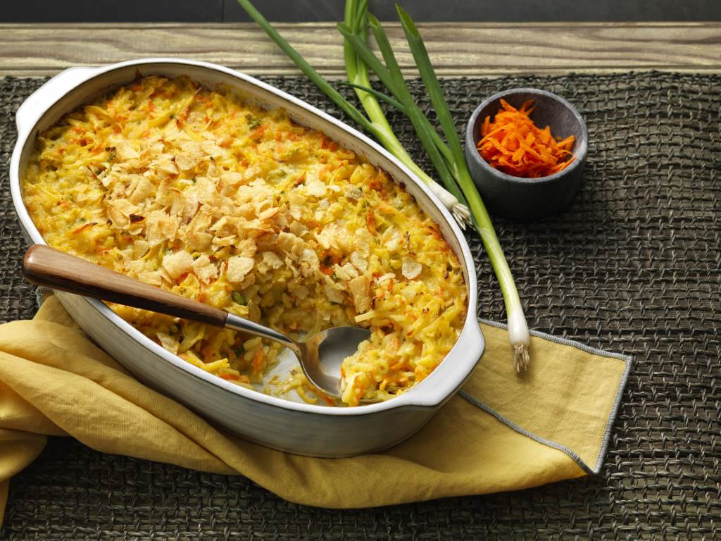 Cheddar Potato Carrot Casserole in pan with spoon for serving