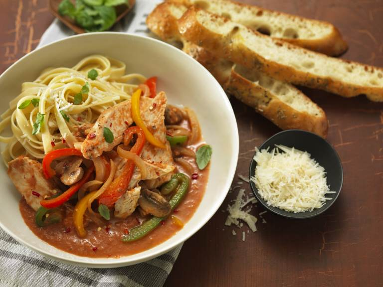 Chicken Cacciatore served in a bowl with bread on side and small bowl of grated cheese
