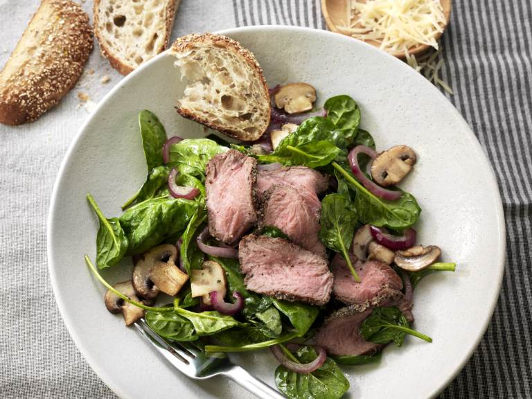 Warm Steak and Spinach Salad on plate with bread on side